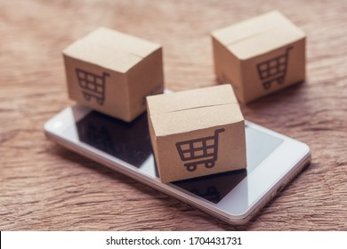 Online shopping - Paper cartons or parcel with a shopping cart logo and smartphone on wood table top. Shopping service on The online web and offers home delivery.