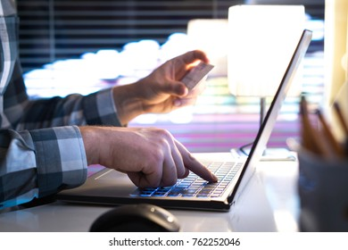 Online shopping and paying with credit card and laptop. Man buying on an internet store in modern home office late at night. Typing login information, pin code and password.