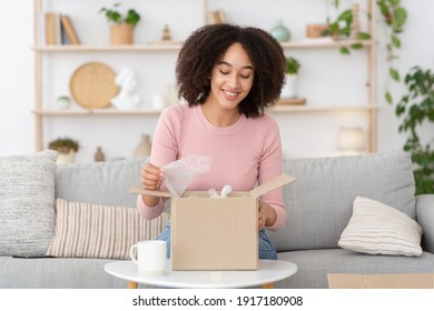Online shopping, pleasure of buying, parcel delivery, good service. Happy interested young african american lady opens cardboard box and looks inside, sits on sofa in living room interior, free space
