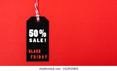 Online shopping, Promotion Black Friday Sale 50% text on black tag on red background.