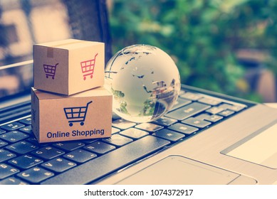 Online shopping / retail ecommerce and delivery service concept : Boxes with a shopping cart sign on a laptop keyboard, depicts consumers purchase or order products from suppliers or digital stores.