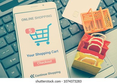 Online shopping / retail ecommerce and delivery service concept : Moblie with shopping app, a credit card on a laptop, depicts consumers purchase or order products from suppliers or digital stores.