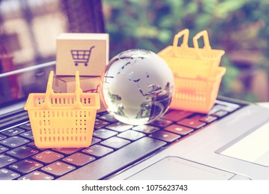 Online shopping / retail ecommerce and delivery service concept : Baskets, boxes with a shopping cart sign on a laptop, depicts consumers purchase or order products from suppliers or digital stores.