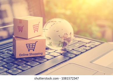 Online shopping / retail ecommerce and delivery service concept : Boxes with a shopping cart sign, globe map on a laptop, depicts consumers purchase or order products from suppliers or digital stores.