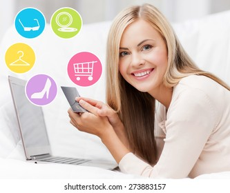 online shopping, sale, fashion and people concept - happy woman or housewife with laptop and credit card at home