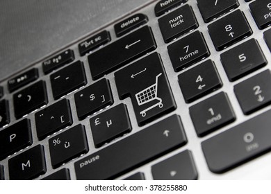 Online shopping, shown by a shopping icon on the Enter key of a minor reflective keyboard.