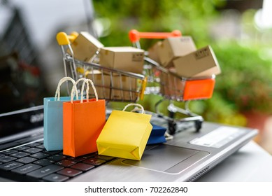 Online shopping from sites via the internet concept : Color paper shopping bags and boxes in shopping carts on a laptop computer keyboard. Consumers always shop goods and things online via internet.