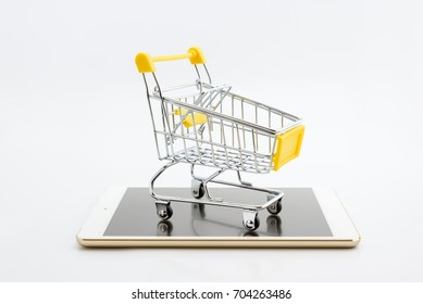 Online shopping with smart mobile device via internet concept : Empty yellow shopping cart on a white smart tablet. Online shopping gains more popularity today due to its convenience and time saving.