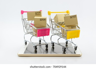 Online shopping with smart mobile device via internet concept : Chromium plated shopping cart on white smart tablet. Online shopping gains more popularity today due to its convenience and time saving.