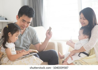Online shopping with tablet pc and credit card. Happy Asian family at home, natural living lifestyle indoors.