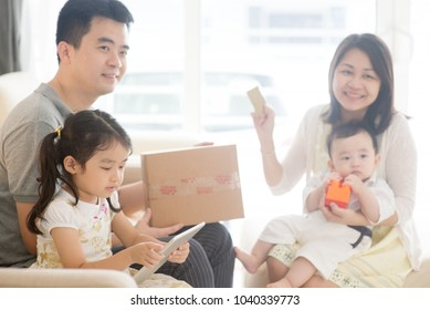 Online shopping using digital tablet pc and payment with credit card. Happy Asian family at home, natural living lifestyle indoors.