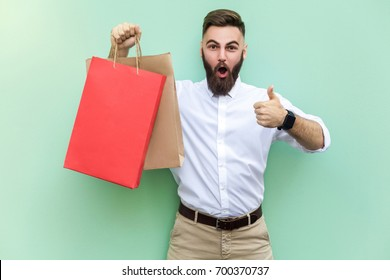 Online shopping. Young adult businessman thumbs up and looking at camera with surprised face. Indoor, studio shot on light green background