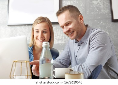 Online shopping. Young happy people buy at the online store. The woman and the man are working together on the computer.
