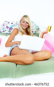 Online shopping - young smiling woman sitting with laptop computer and credit card in her hand.