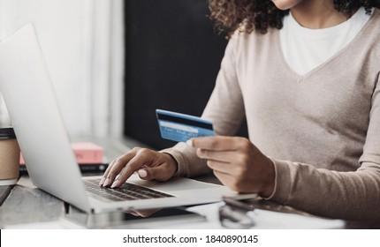 Online-Shopping. Junge Frau mit Kreditkarte und Laptop zu Hause