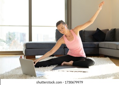 Online sport fitness yoga training workout. young woman and doing exercises on yoga mat opposite laptop at home