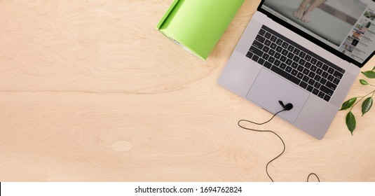 Online sports or yoga training concept Laptop with yoga mat  and microphone on the table top view