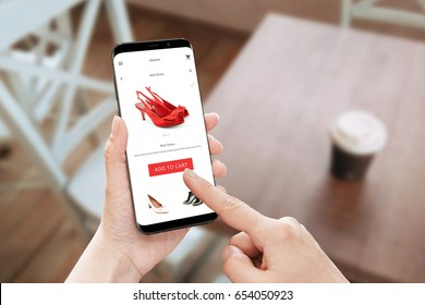 Online store app use on modern mobile phone with round edges. Woman touch add to cart button for red shoes.