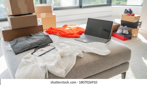 Online store selling new clothes from home. Small business working on laptop shopping for fashion clothing shipped in shipping cardboard boxes.