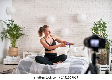 online stream coach shows technique exercise massage ball. relaxation of the muscles of the hand with a massage ball. in a modern home environment, the girl writes a video blog self massage
