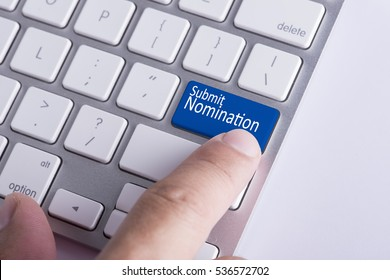 Online Submission Concept: Finger pressing Submit Nomination button on Keyboard