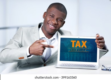 Online Tax payment concept. Handsome businessman with laptop, close up