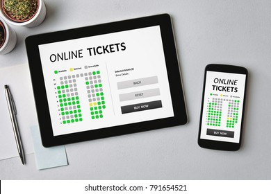 Online tickets concept on tablet and smartphone screen over gray table. All screen content is designed by me. Flat lay