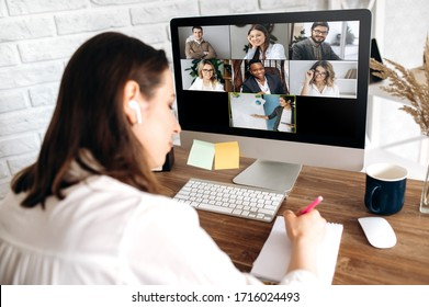 Online training. The back view of a girl who learns online by video conference online. On the screen, the teacher tells the information to her and other participants in the conference
