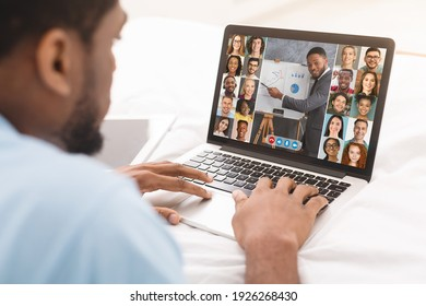 Online Training. Black Man Watching Web Conference With Group Of Business People And Financial Coach While Lying With Laptop Computer In Bed, African Man Enjoying Distance Learning, Creative Collage