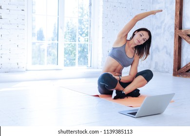 Online training. Delighted sportswoman crossing legs while sitting on the mat and doing stretching exercises