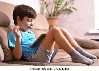 Online training education and communiction. Quarantine. Happy smiling kid boy waving hand to call on tablet. Stay home preparing home task