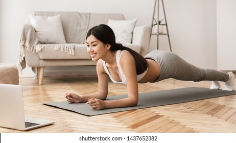 Online Training. Girl Exercising at Home, Doing Plank and Watching Videos on Laptop