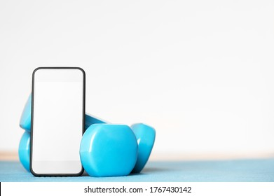 Online training. Sport tools for workout at home. Dumbbells and smartphone with empty screen. Mockup on display of cellphone. Healthy lifestyle. Isolation period. Home exercises concept