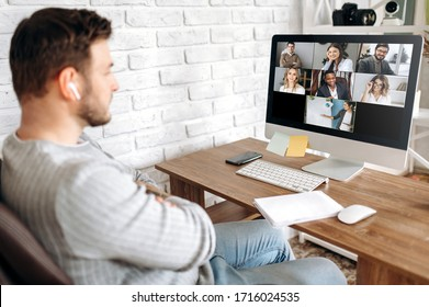 Online training. Young guy learns online by video conference in zoom app. On the screen, the teacher tells the information to him and other participants in the conference