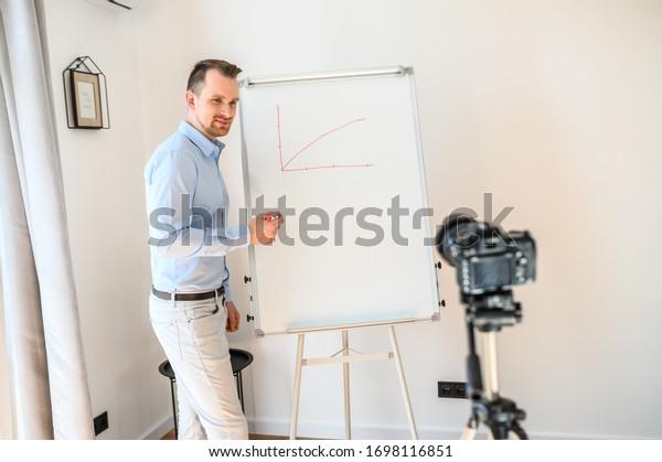 Online-Tutor, Lehrer, Mentor. Positiver Typ in formellen Hemden steht mit einem Marker in der Hand nahe weißes Brett, sieht Kamera auf Stativ und lächelt. Er gibt eine Videostunde. Konzept des Online-Studiums