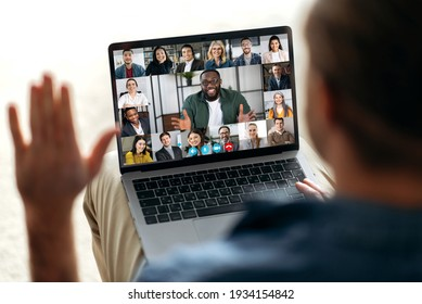 Online video communication concept. Over shoulder view at a laptop screen with different people, employees, business partners, guy greets colleagues, online briefing, brainstorming, group teleworking