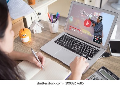 Online video tutorial concept.Female using laptop or pc on wooden table