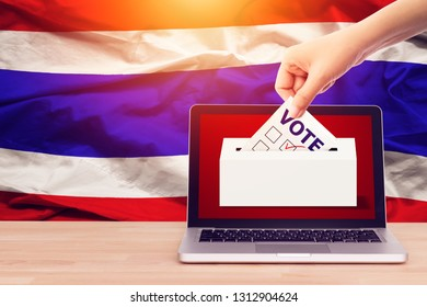 online vote , poll, exit poll for Thailand general election concept. close up hand of a person casting a ballot at elections during voting on canvas Thailand flag background.