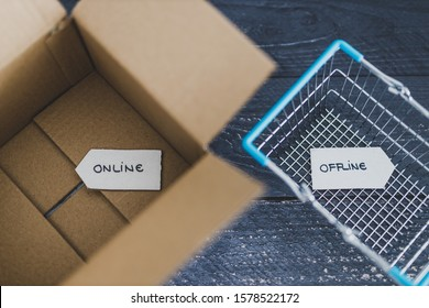 online vs retail shopping conceptual still-life, parcel and shopping basket with Online and Offline signs