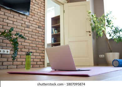 Online workout at home gym concept. Laptop computer on yoga mat on floor in living room in modern apartment interior. Internet fitness training classes remote technology video sport exercises routine