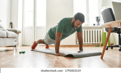 Online workout. Male fitness instructor showing push up exercises while streaming, broadcasting video lesson on training at home using laptop. Sport, online gym concept. Web Banner