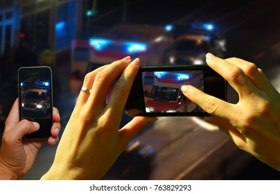 Onlookers film an accident scene with the cell phones