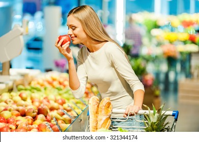Only the best fruits and vegetables. Beautiful young woman holding apple and smelling it with smile while standing in a food store