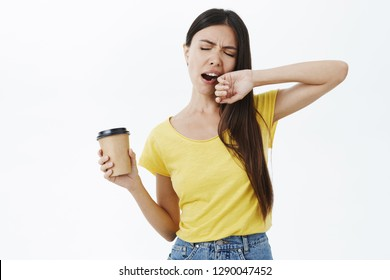 Only coffee can fight sleep. Tired and sleepy cute female coworker in yellow t-shirt yawning with closed eyes covering opened mouth with arm holding paper cup of caffeine waking up on way to office