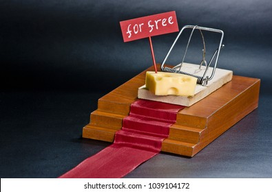 The only free cheese is in the mousetrap: mousetrap with cheese on the red carpet and free sign on the isolated black background.