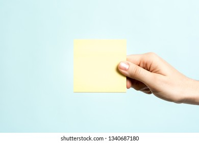 Only one hand showing a yellow empty sticky note for text on blue background