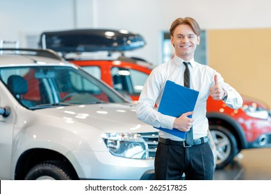 Only perfect cars. Young smiling salesman standing with a clipboard in his hands and showing his thumb up in car dealership