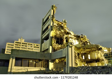 Only small part of a destroyed building still standing. Roof and most of the walls have collapsed. Dramatic night scene of a demolished concrete building.