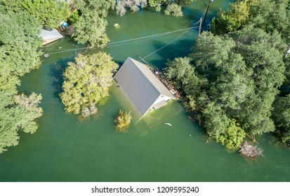 Only the top of the rooftop above the water, Historic Flooding aerial drone view above Homes and Houses under water after Central Texas Flooding
