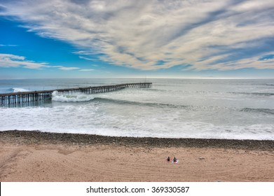 Only two beach goers watching the waves brush the bottom of the Ventura pier.